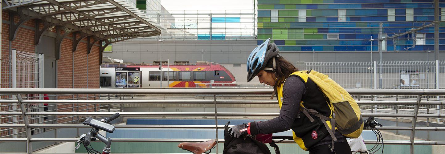 Sobre la bicicleta i amb equipatge a l'estació de trens
